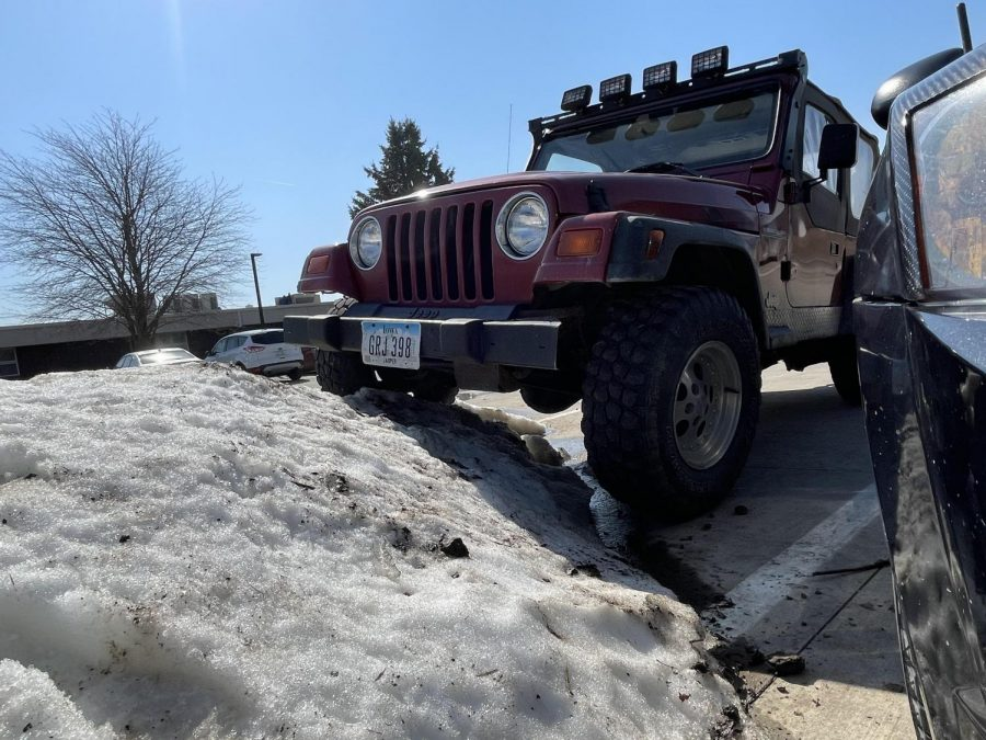 Trevor Buckingham's Jeep TJ tackles snow piles in PCM parking lot.